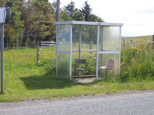An enclosed bus shelter along a country lane with two chairs that someone has put there out of necessity